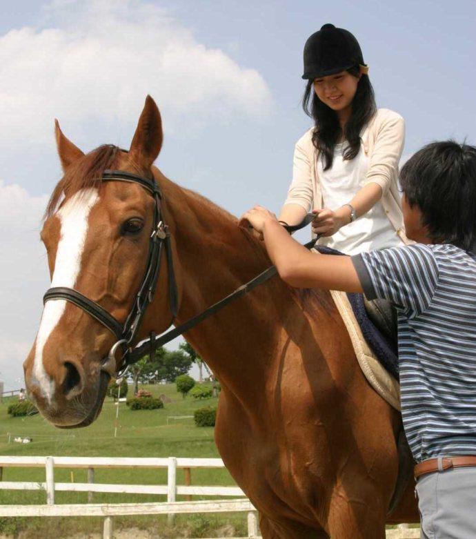 「愛知牧場」で予約すると体験できる乗馬レッスンを満喫する女性