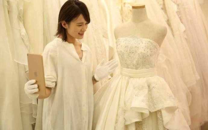 東京都渋谷区にあるaim東京原宿店でアドバイザーがドレスを案内する様子
