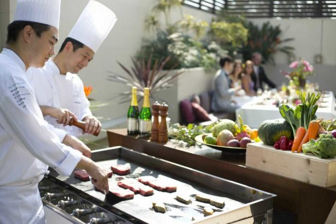 ガーデンでお肉の鉄板焼きを提供するアイルバレクラブの料理スタッフ