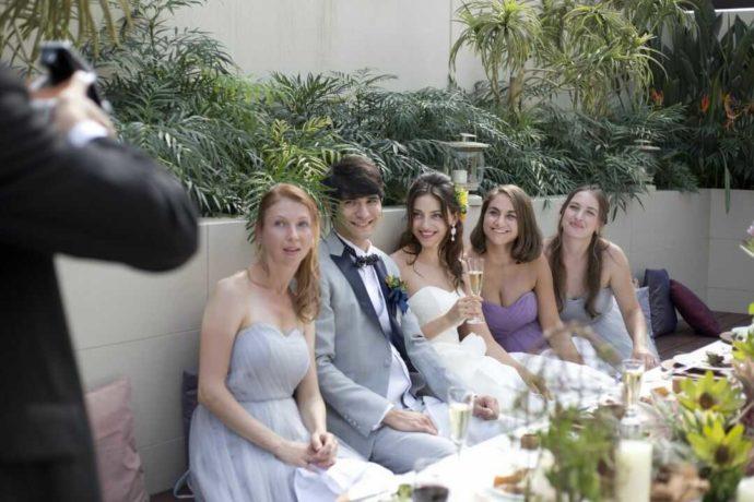 アイルバレクラブのガーデンにあるソファで写真撮影をする新郎新婦と友人