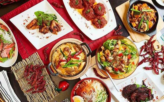 東京都港区にある「赤い壺」の複数の人気料理がテーブルの上に並んでいる様子
