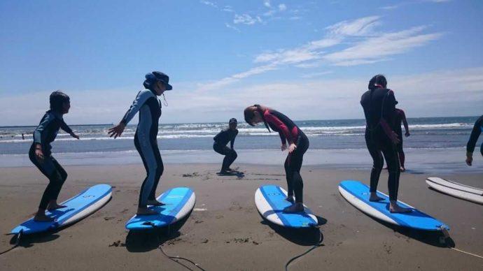 大洗海の大学のサーフィン教室でサーフィンを楽しむ女性たち