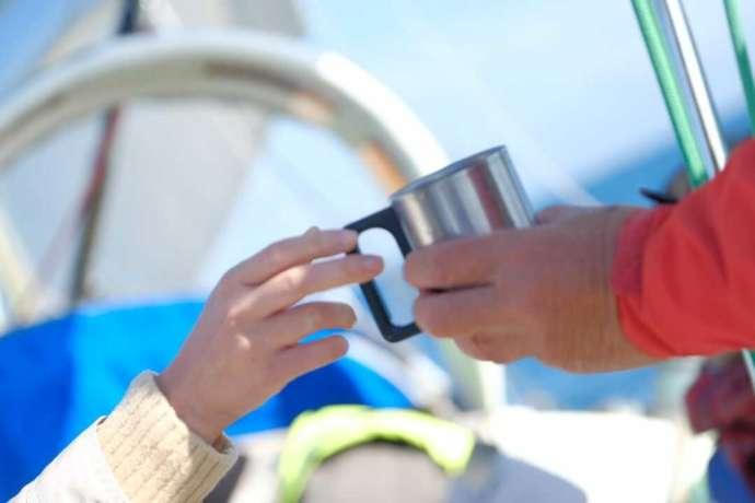 大洗海の大学のヨットクルージングの船上でドリンクを飲んでホッと一息