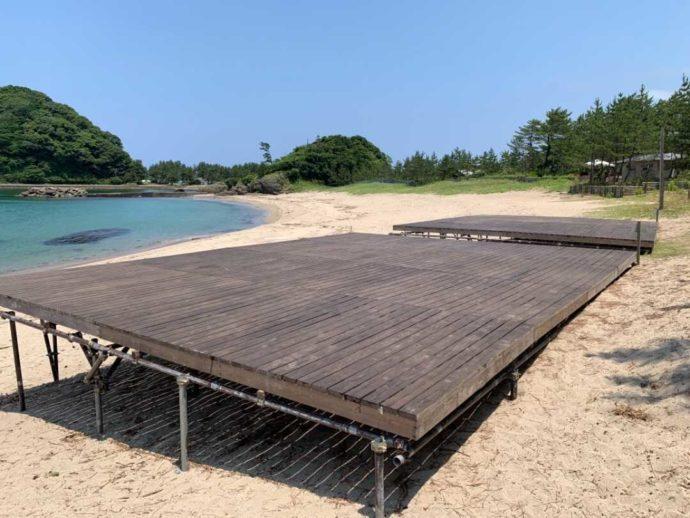 弁天浜キャンプ場にあるビーチサイドデッキサイト越しに海と砂浜を望む