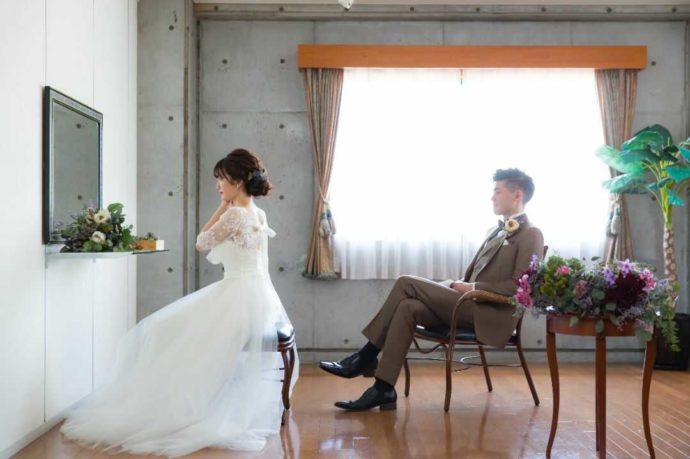 「ぶどうの木ウェディング」の支度部屋で挙式の準備をする新婦と座って見守る新郎