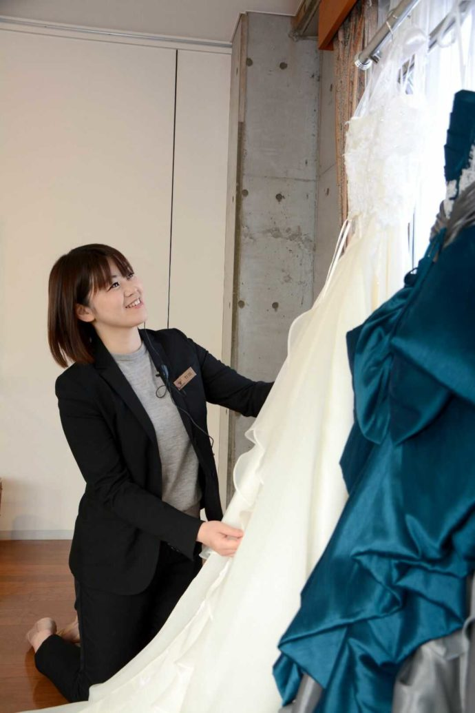 新婦のドレスを笑顔で見つめながら準備するマネージャー兼ウェディングプランナーの竹田さん