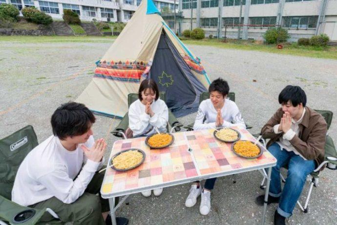 「キャンピース」のグラウンドでキャンプ飯を食べる4人