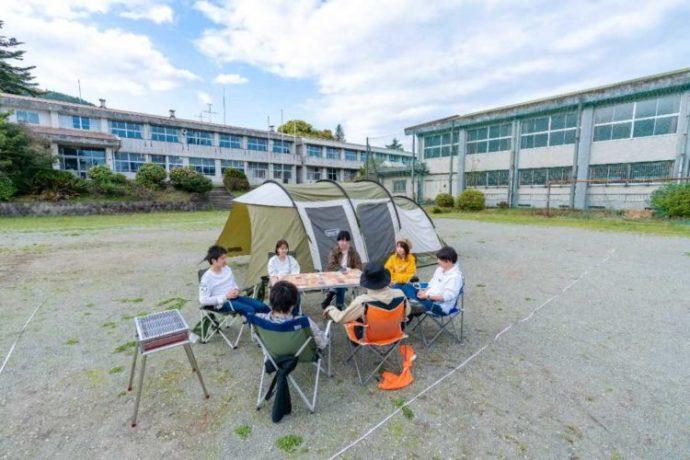 テントサイトのグラウンドでキャンプを楽しむ若者7名