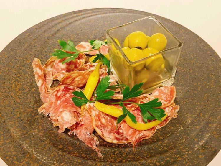 港区にある「dot&blue」の定番の組み合わせ料理のアンチョビ入りグリーンオリーブとバスク豚の熟成サラミ
