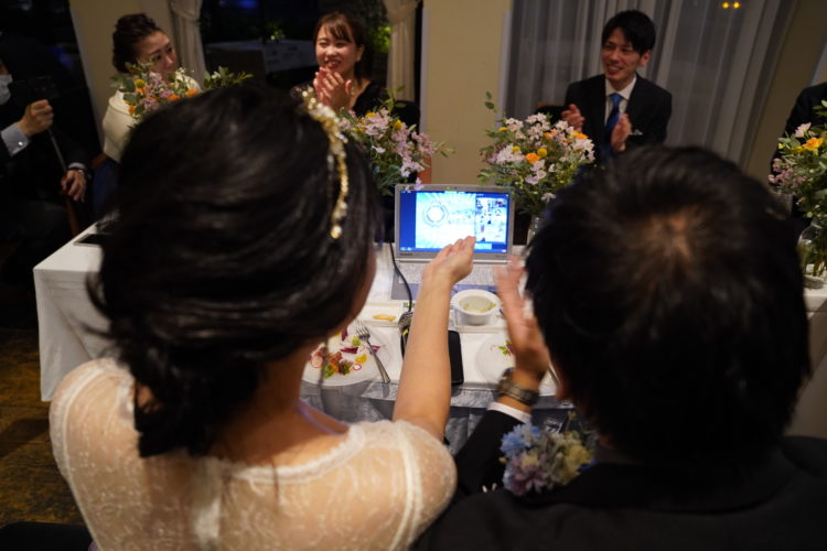 「EMOTIONAL PARTY!」のオンライン結婚式で画面を見ながら盛り上がる新郎新婦