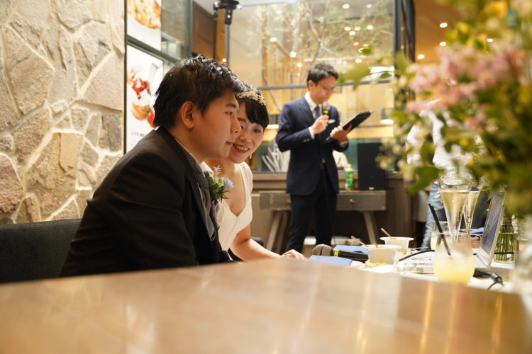 「EMOTIONAL PARTY!」のオンライン結婚式で仲良く画面を見る新郎新婦