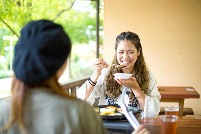 堺・緑のミュージアム ハーベストの丘内のバーベキューレストランで食事をする女性