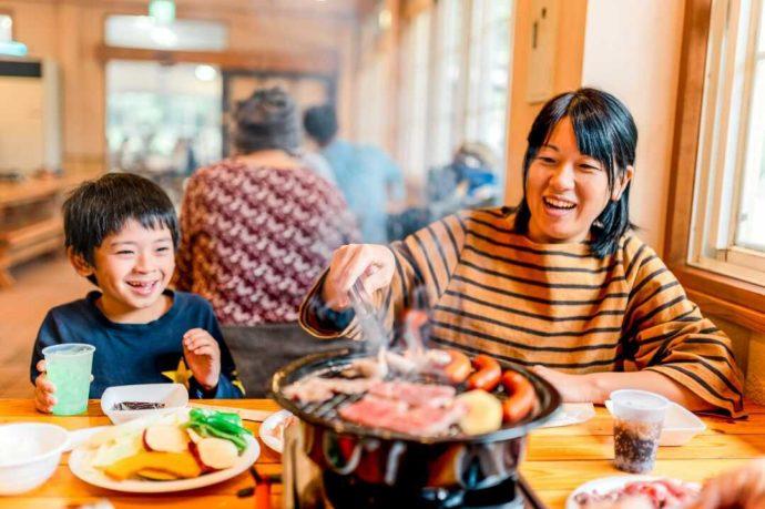 バーベキューレストランで肉を焼き、笑顔で食事中の親子