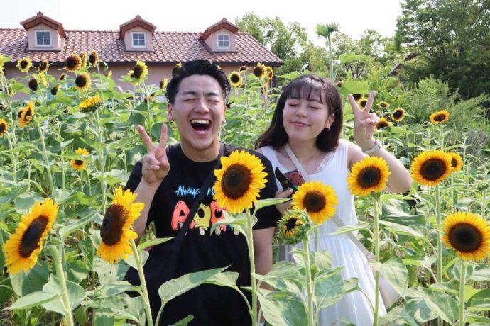 ひまわり畑で記念写真を撮るカップル