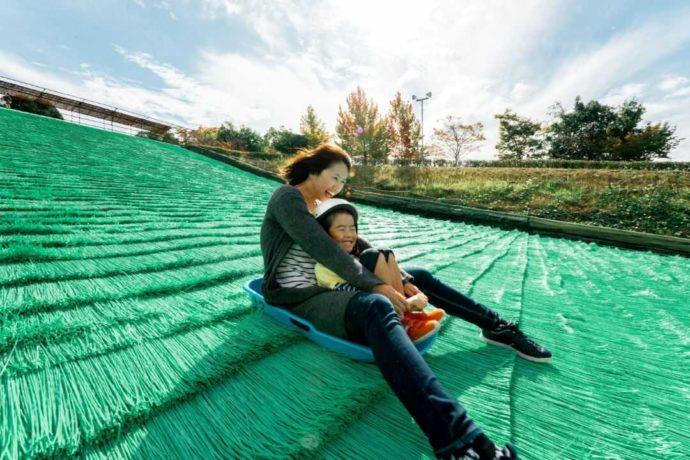堺市の「ハーベストの丘」で芝すべりを楽しむ親子
