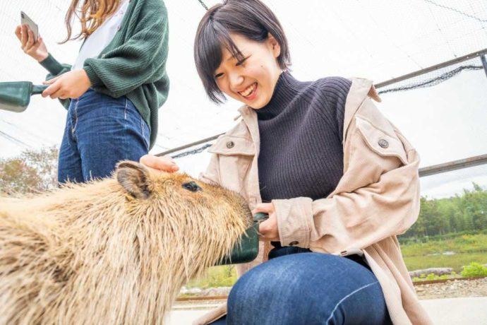 堺・緑のミュージアム ハーベストの丘でカピバラふれあい体験に参加し笑顔の女性