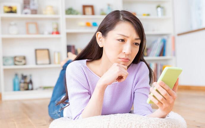 女性がスマホを見ながら不満そうにしている時のイメージ
