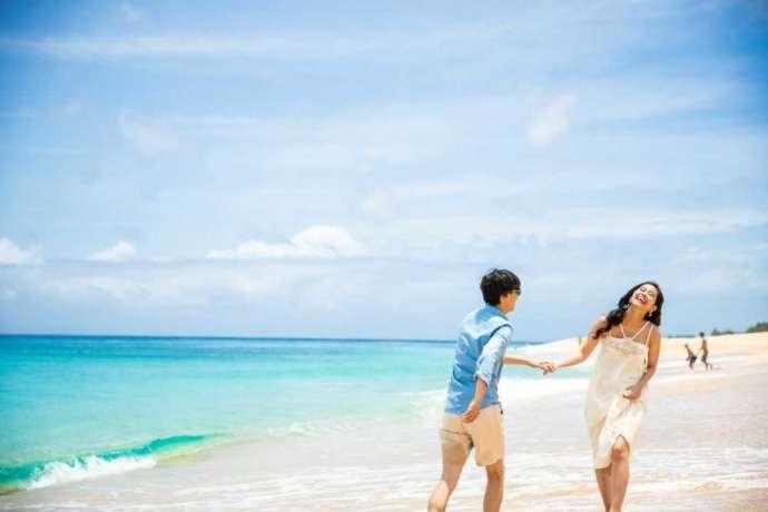 ハワイの海辺で手をつないでいる新郎新婦