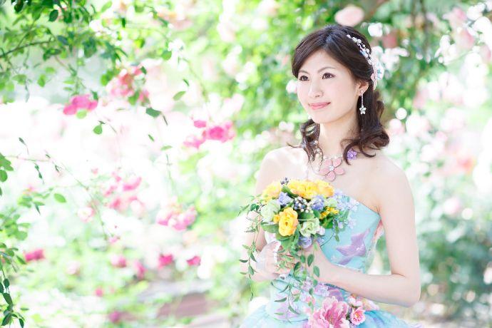 バラ園でブーケを持つ花嫁