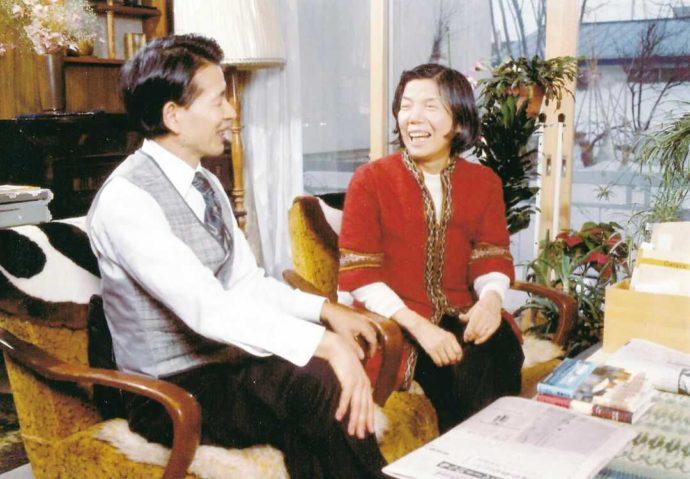 居間で笑顔を見せる三浦夫妻の写真