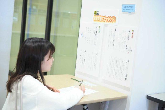 漢検 漢字博物館・図書館(漢字ミュージアム)の検定問題に挑戦する女性