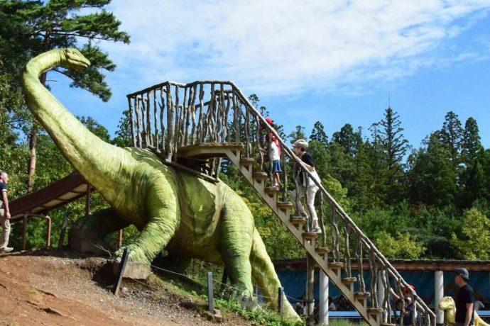 かつやま恐竜の森にあるスギヤマリュウ滑り台で遊ぶ子どもたち