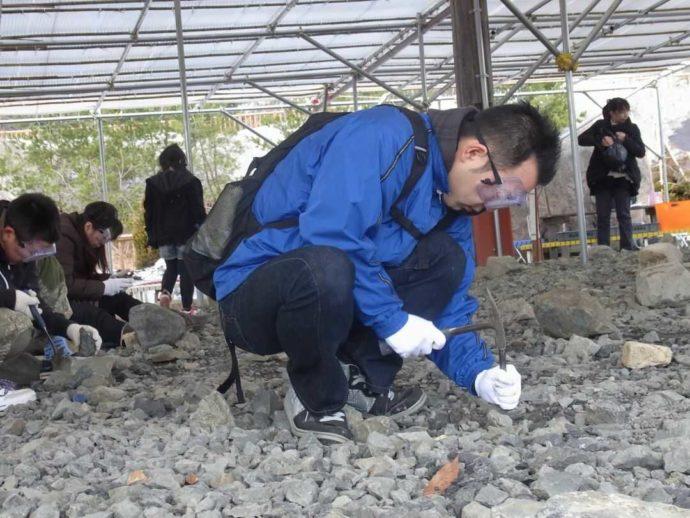かつやま恐竜の森で雨の日に化石発掘体験を楽しむ参加者たち