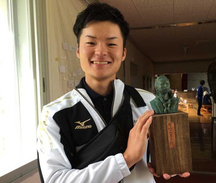 小さな銅像を持って微笑む「剣淵町郷土資料館」の男性スタッフ