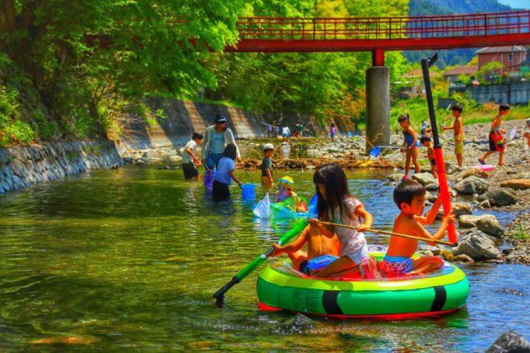 ケニーズ・ファミリー・ビレッジ/オートキャンプ場の川で遊ぶ人々