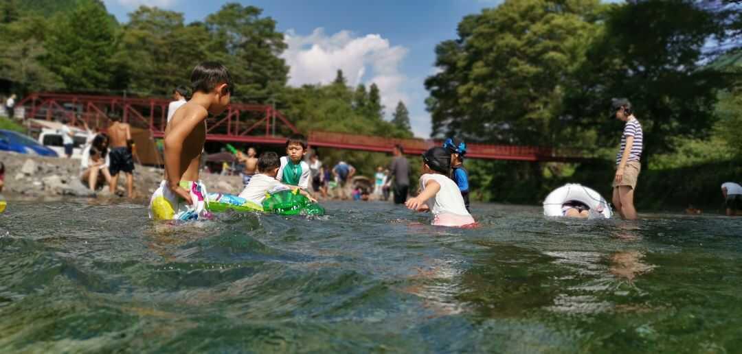 ケニーズ・ファミリー・ビレッジ/オートキャンプ場の天然プールで遊ぶ人々