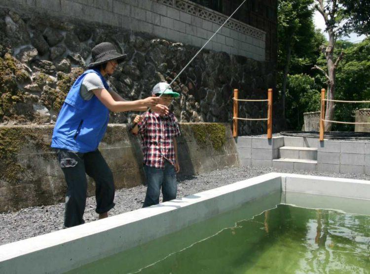 ケニーズ・ファミリー・ビレッジ/オートキャンプ場で釣りをしている親子