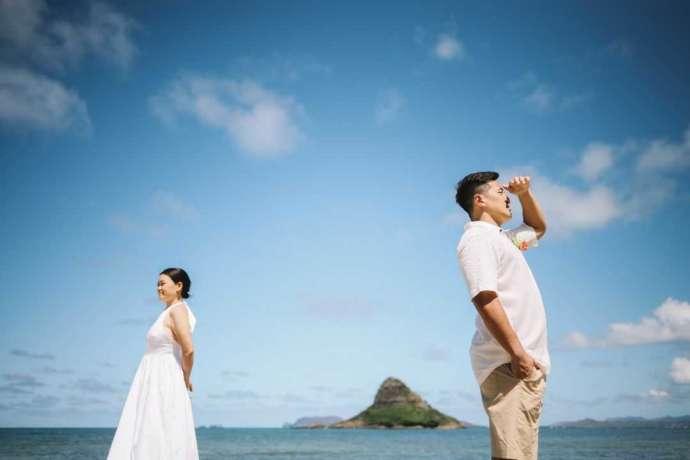 島が見える海辺で写真撮影をする新郎新婦
