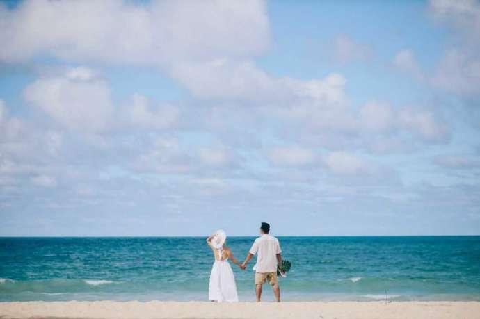 手を繋いでハワイの海を望む新郎新婦