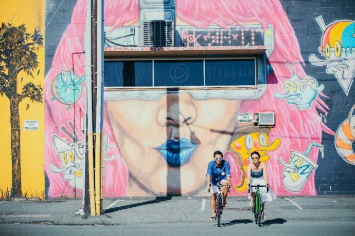 ストリートアートをバックに自転車に乗る新郎新婦