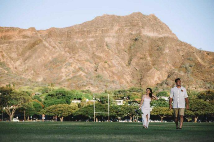 大きな岩山をバックに歩く新郎新婦