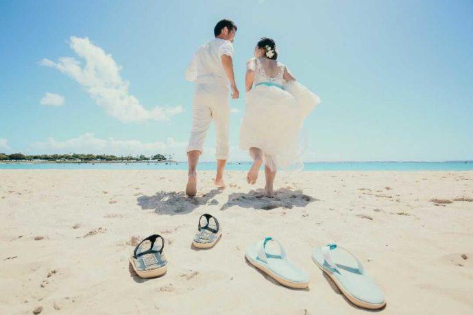 ハワイのビーチで海に走る新郎新婦