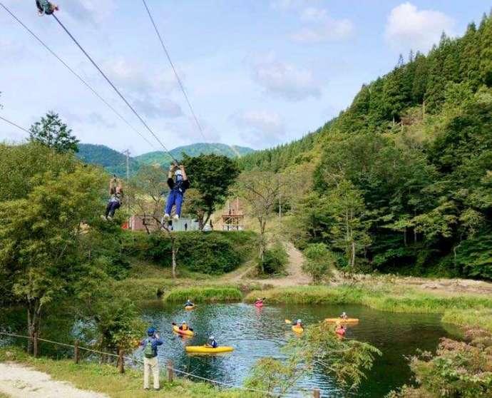 めいほう高原キャンプフィールドの人気アクティビティの「アクアジップライン」と「カヌー」を楽しむ人々