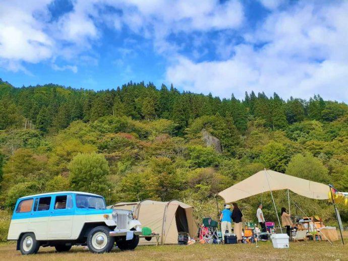 岐阜県「めいほう高原キャンプフィールド・バーベキューパーク」のオートサイトと車とキャンプを楽しむ人たち