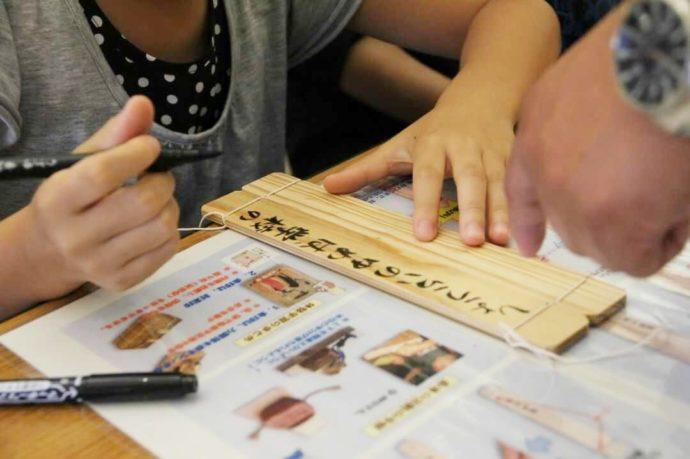 封泥体験で木板に文字を書く女の子