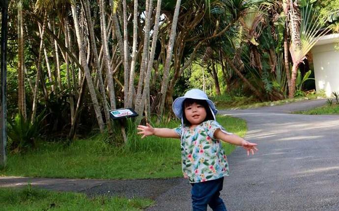 ネオパークオキナワの熱帯の植物と写真を撮る少女