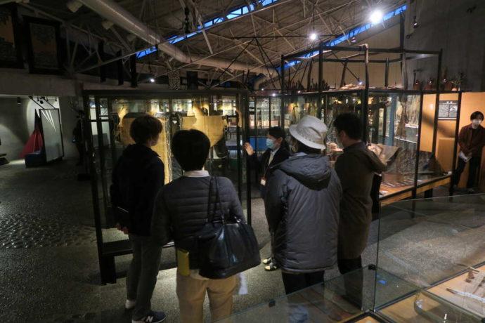 平取町立二風谷アイヌ文化博物館のスタッフの話に耳を傾ける来館者たち