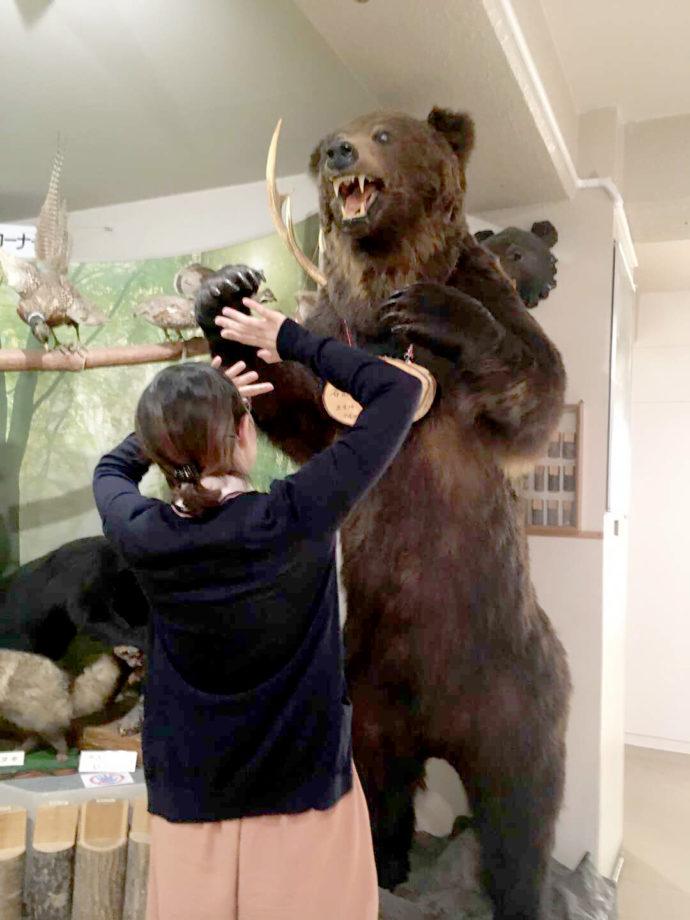 登別市郷土資料館にあるヒグマのはく製の前でびっくりしたようなポーズの学芸員