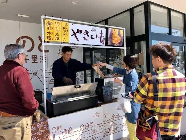 道の駅「のと千里浜」の軒下で焼き芋を販売する人と客3人