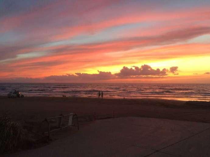 千里浜にあるなぎさドライブウェイで夕焼け空を眺める2人