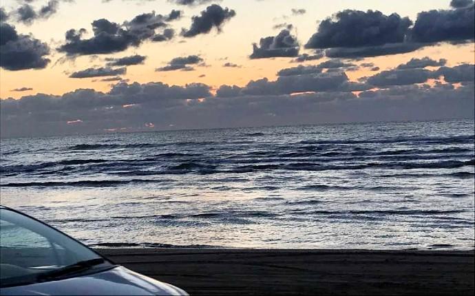 千里浜にあるなぎさドライブウェイの夕焼け空と停車する1台の車の一部