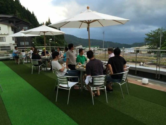 野沢温泉スパリーナのテラスで食事をする男性グループ