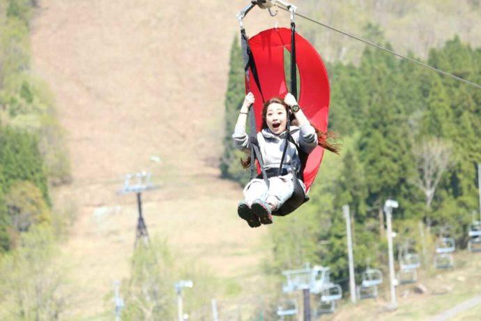 野沢温泉スポーツ公園の「ジップ・スカイライド」を楽しむ女性
