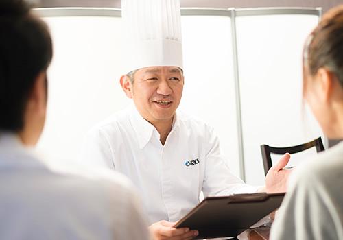 オークスカナルパークホテル富山の料理長が新郎新婦と料理の打ち合わせをしている場面
