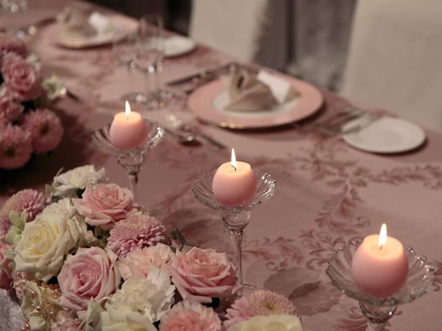 テーブルの上に置かれているピンク系の花やキャンドル