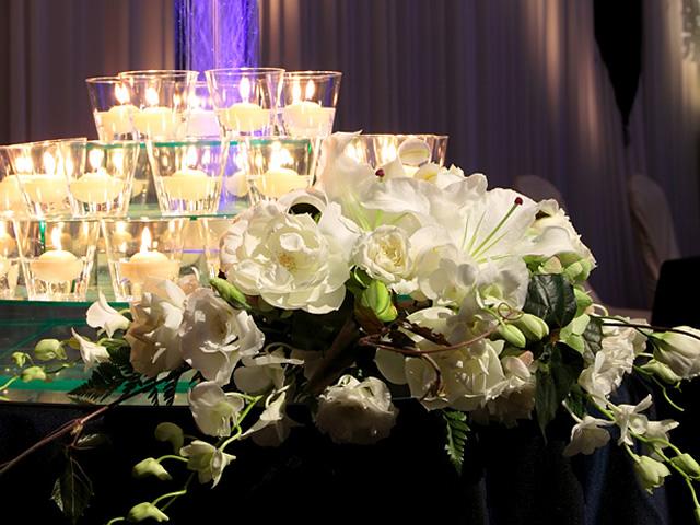 テーブルの周りを飾る白の花やガラスに入ったキャンドル